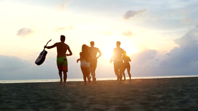 Group of friends running on the beach at sunset Group of friends running on the beach, ready to party at sunset by the sea. They walk on the sand with barefoot, moving dust in the warm sunset light. party social event stock videos & royalty-free footage