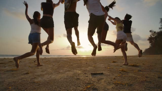 slow motion - group of friends running on the beach at sunset with happy emotion. people with party celebration concept. back rear view. - student life stock videos & royalty-free footage