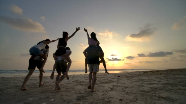 スローモーション-幸せな感情と日没にビーチで実行している友人のグループ。パーティーのお祝いの概念を持つ人々。背面図。 - 学生生活点の映像素材/bロール