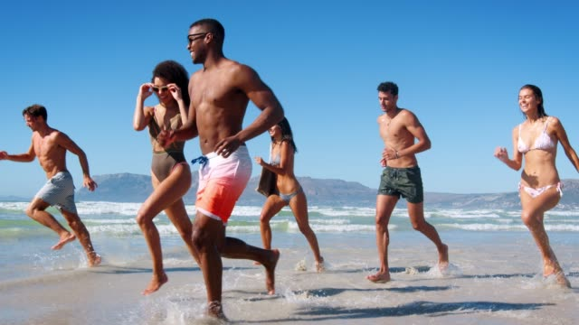 Group Of Friends Running Through Waves On Beach Vacation Side view of group of friends in swimwear running through waves on summer beach vacation - shot in slow motion medium group of people stock videos & royalty-free footage