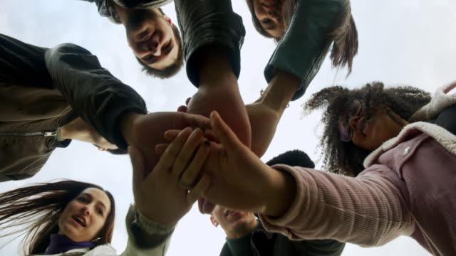 gruppe von freunden zeigen einheit, sie stapeln ihre hände zusammen - hände halten stock-videos und b-roll-filmmaterial