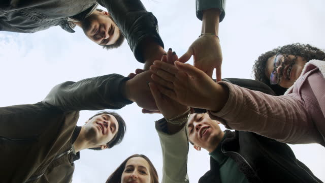 Group of friends showing unity, they are stacking their hands together video