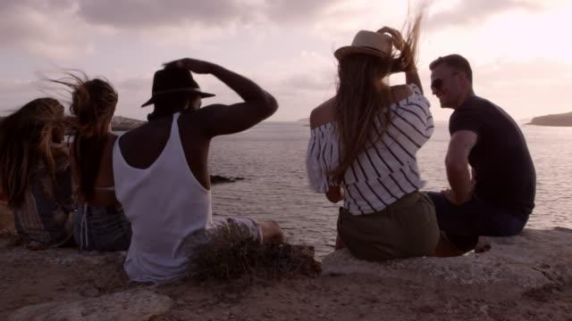 vídeos de stock e filmes b-roll de group of friends sit on cliff watching sunset shot on r3d - ibiza