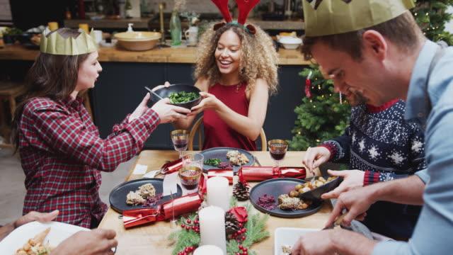 gruppo di amici seduti intorno al tavolo da pranzo a casa mentre viene servita la cena di natale vegetariana - pranzo di natale video stock e b–roll