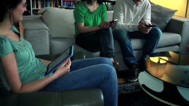 Group of friends sitting in living room with technology video