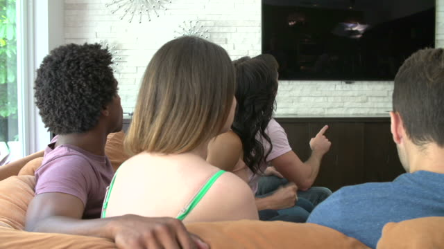 Group Of Friends Sitting On Sofa Watching TV Together video