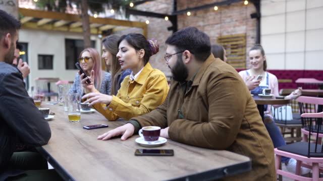 gruppe von freunden sitzt im freien in der kneipe - kräftig gebaut stock-videos und b-roll-filmmaterial
