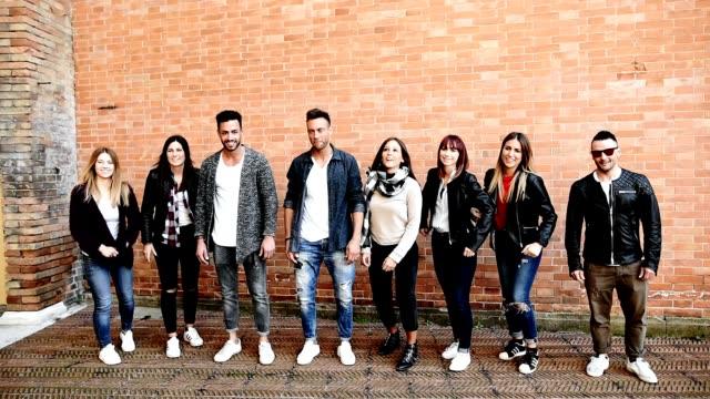 grupo de amigos, todos juntas contra uma parede a sorrir - vídeo