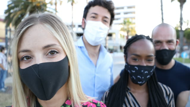 Group of friends smiling to the camera wearing protective face masks
