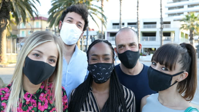 Group of friends smiling to the camera wearing protective face masks - video