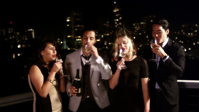 A group of friends stand on a roof at night and drink a bottle of champagne in celebration video
