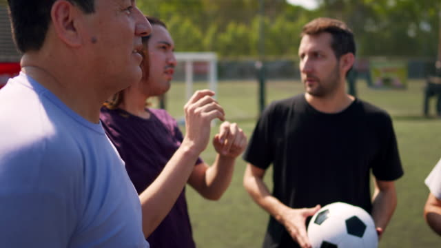 Group of friends standing on soccer field, talking and having fun Group of friends standing on soccer field, talking and having fun pre game stock videos & royalty-free footage