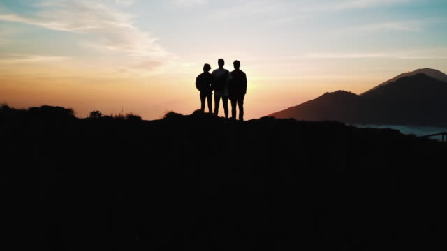 Group Of Friends Standing On Top Of Mount Batur In Bali Looking Out The View At Sunrise 4K Group Of Friends Standing On Top Of An Active Volcano In Bali, Indonesia Whilst Looking Out The View At Sunrise silhouette people stock videos & royalty-free footage
