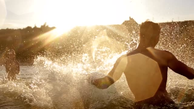 Group of friends swimming in the sea at sunset getting wet and making splashes in slow motion. Young people having fun in the water Group of friends swimming in the sea at sunset getting wet and making splashes. Young people having fun in the water. swimming stock videos & royalty-free footage