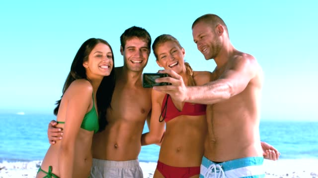 Group of friends taking self pictures on the beach video