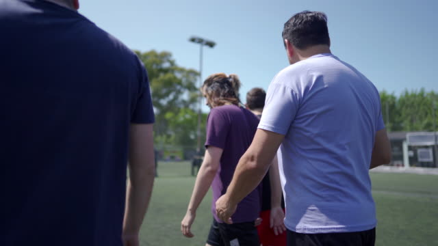Group of friends talking about tactics before the start of the match Rear view of male friends walking down soccer field and talking about tactics before the start of the match pre game stock videos & royalty-free footage