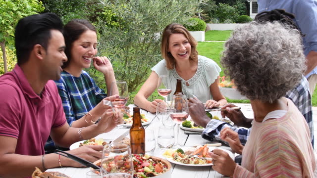 Group of friends talking and relaxing together over lunch outdoors video