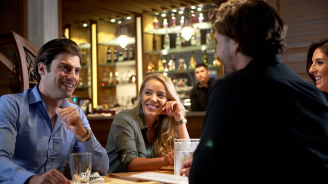 vídeos de stock e filmes b-roll de group of friends talking in a restaurant - happy hour