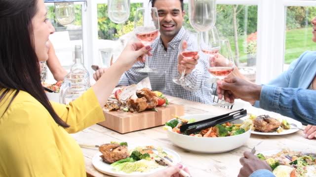 grupp vänner rosta och dricka rosévin under middagen - vin sommar fest bildbanksvideor och videomaterial från bakom kulisserna