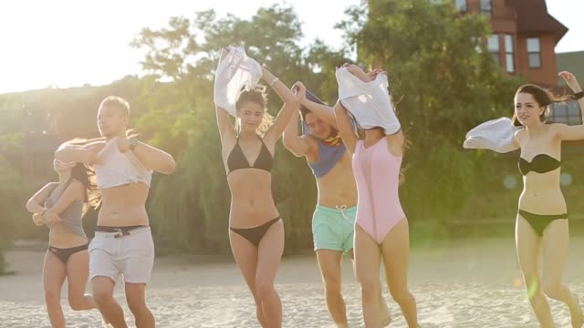 group of friends undress running into the sea water on sunset and throw shirts on the beach. cheerful happy people having fun on the beach. men and women go to swim in slow motion - koszula filmów i materiałów b-roll