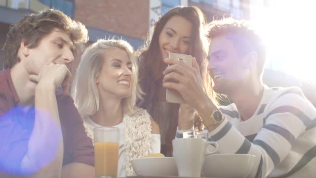 Grupo de amigos usando o telefone durante o dia de sol. - vídeo
