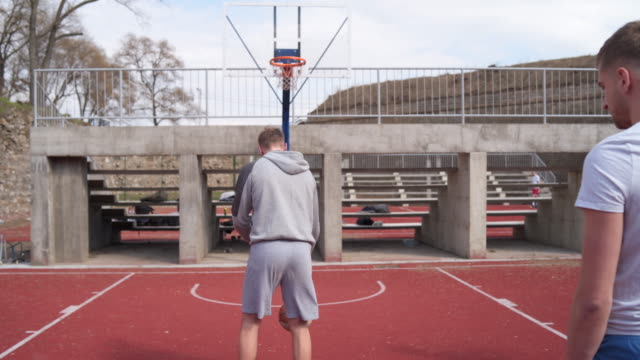 Group of friends warming up before basketball game Group of young adults playing amateur basketball outdoor practice drill stock videos & royalty-free footage