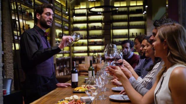 vídeos y material grabado en eventos de stock de grupo de amigos degustación de vinos en la enoteca con un sumiller guiando la clase - comida gourmet