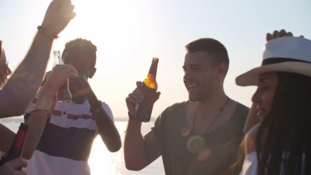 gruppe von freunden mit bier party am strand - spring break stock-videos und b-roll-filmmaterial