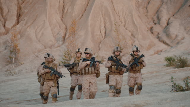 Group of Fully Equipped and Armed Soldiers Walking Forward towards Camera in Desert Environment. video