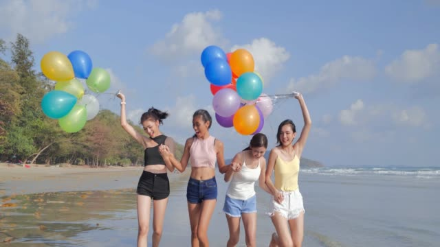 Group of girlfriends walking on the beach with a balloon against a background of a blue sky.Happiness Friends fun on the beach under sunset sunlight in summer sunny day.Vacations - iStock - vídeo
