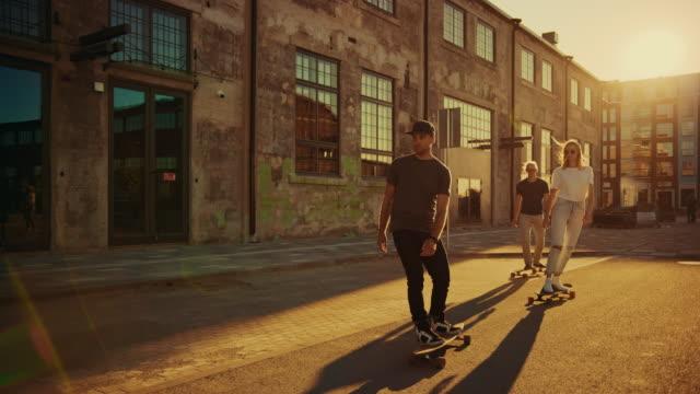 一組女孩和男孩在滑板通過時尚嬉皮士區。美麗的年輕人滑板通過現代時尚城市街。移動慢動作相機拍攝。黃金時間 - 都市生活 個影片檔及 b 捲影像