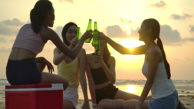 女の子の友人のグループは、ドリンクを楽しんで、日没時にビーチでリラックスする楽しみを持っています。パーティー祝賀コンセプトの人たち。スローモーションショット。 - 飲み会点の映像素材/bロール