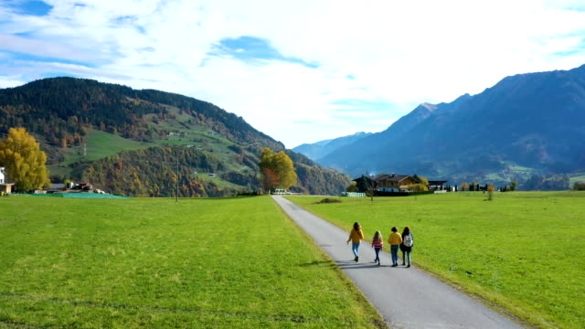 group of girls walking by the road between green fields at the austrian Alps at sunny autumn day
