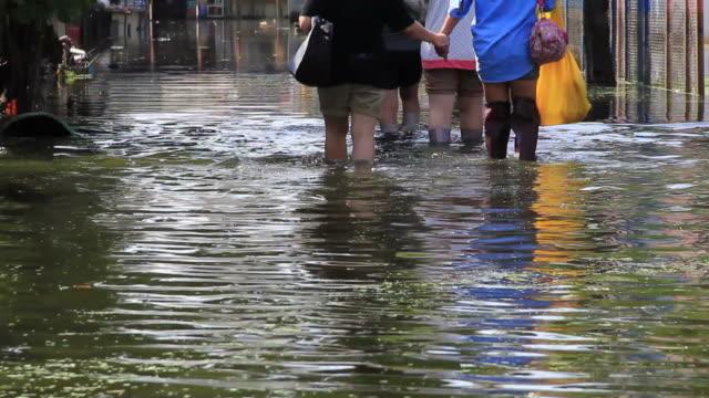 группа девочек ходить на наводнения road. - сила природы стоковые видео и кадры b-roll