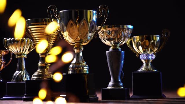 vídeos de stock, filmes e b-roll de grupo de troféu de ouro no fundo preto - troféu