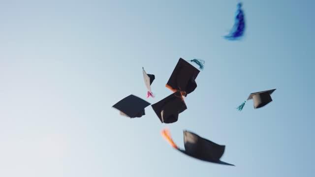 vídeos y material grabado en eventos de stock de un grupo de graduados arrojó sus sombreros al cielo para felicitarlos por la graduación. - graduación