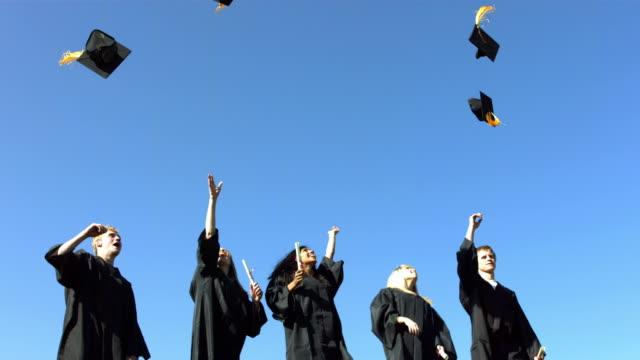 group of graduates throwing graduation caps - graduation cap stock videos & royalty-free footage