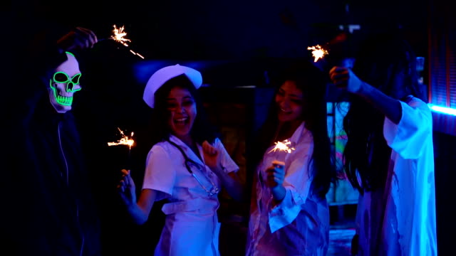 Group Of Happiness Friends In Halloween Costumes Playing Sparklers While Celebration Halloween Time At A Halloween Party