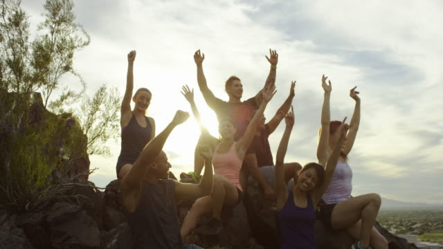 Grupo de pessoas felizes juntos no topo de uma colina comemorando. - vídeo