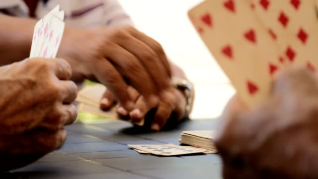 Group Of Happy Elderly People Playing Cards And Laughing Active retired people, senior friends and free time, old latino men having fun and playing game of cards. Leisure, recreation, retirement. Over the shoulder view of hands holding card playing card stock videos & royalty-free footage