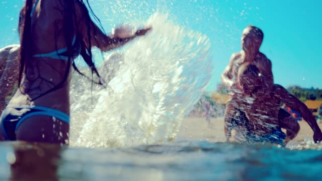 Group of happy friends guys and girls playing in water at the beach Group of happy friends guys and girls playing in water at the beach swimwear stock videos & royalty-free footage