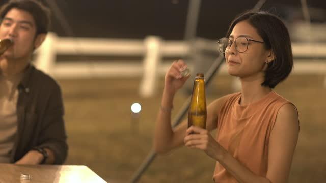 stockvideo's en b-roll-footage met groep gelukkige vrienden die pret samen hebben, het drinken van gebotteld bier in het kamperen, het vieren, gelukkig glimlachen - vriendschap, saamhorigheidsconcept - 20 29 jaar