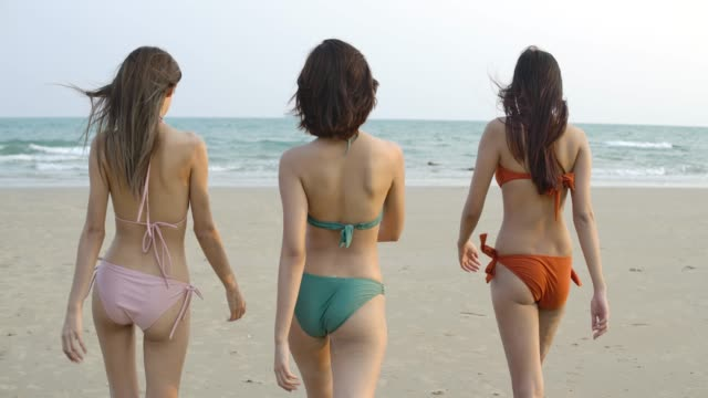 Group of happy girls friends in bikini walking on the beach, Cheerful Women Group Tourists On Summer Holiday. Slow Motion.