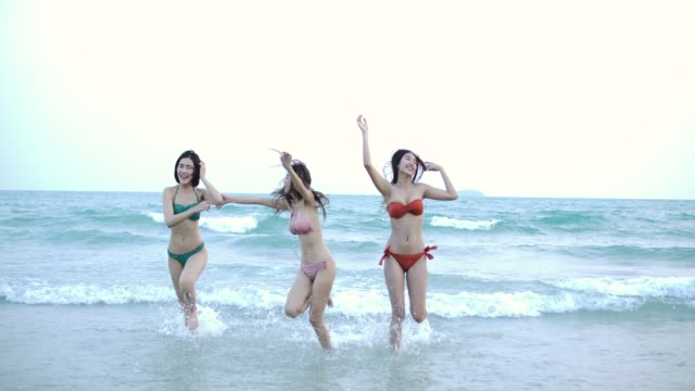 Group of happy girls friends playing in water at the beach. Beautiful asian girl during summer vacation. celebration and relaxation concept.