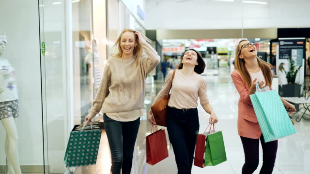 Group of happy girls is having fun in shopping center walking with paper bags, laughing and dancing pointing at goods in shop windows. Youth and shopaholics concept. Group of happy girls is having fun in shopping center walking with paper bags, laughing and dancing pointing at goods in shop windows. Youth lifestyle and shopaholics concept. shopping mall stock videos & royalty-free footage