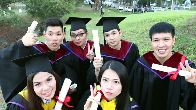Group of happy international students in mortar boards and bachelor gowns with diplomas taking a selfie by small camera outdoors. Education, Graduation, Technology and people concept. Group of happy international students in mortar boards and bachelor gowns with diplomas taking a selfie by small camera outdoors. Education, Graduation, Technology and people concept. international match stock videos & royalty-free footage