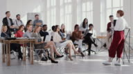 istock RED EPIC Group of happy multiethnic business people listen to female coach speaking at modern office seminar slow motion 1172593878