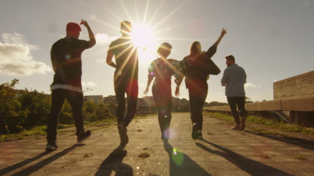 Group of Happy Teenagers Laughing, Raising Hands, Jumping While Moving Outwards Camera.