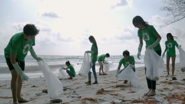 Video Group of happy volunteers with garbage bags cleaning area on the beach.Volunteerism,charity, cleaning, people and ecology concept