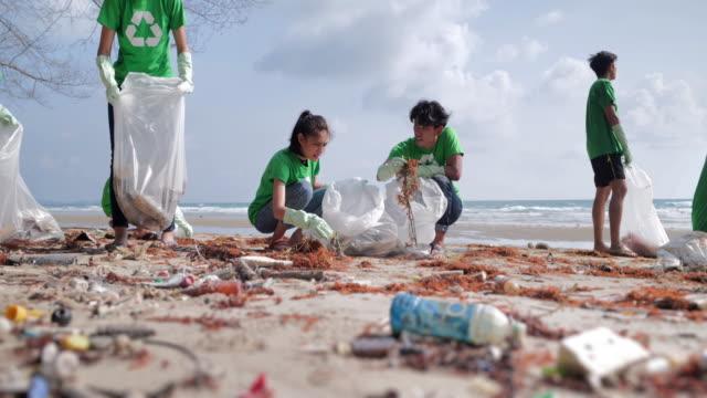 一群快樂的志願者在海灘上帶著垃圾袋清潔區。志願服務、慈善、清潔、人和生態概念。志願服務 - 清新 個影片檔及 b 捲影像